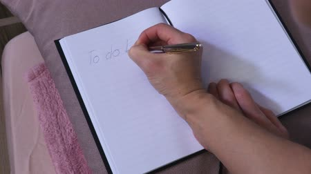 Woman write to do list in notebook