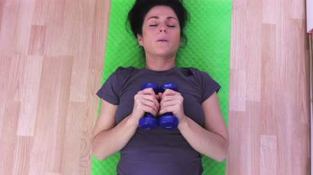 Woman in sportswear doing exercises with dumbbells Dostupné videozáznamy