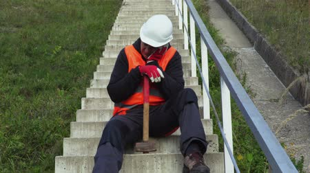 Lazy worker with hammer relax on concrete stairs