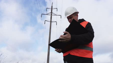 Electrician with documentation near high voltage line