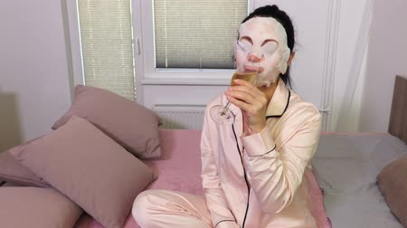 Woman with facial mask drinking champagne