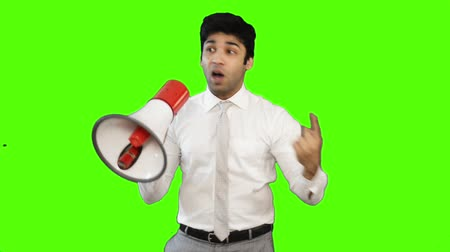 greater : Locked-on shot of a young businessman talking into a megaphone on green background