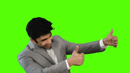 секунды : Locked-on shot of a happy businessman showing thumbs up on green background
