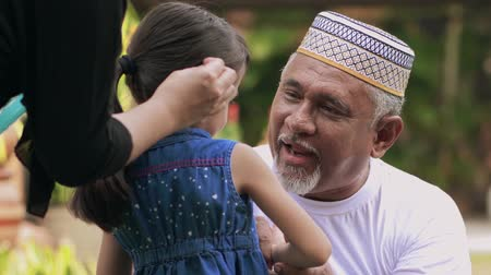 cumprimentar : Senior man excited to meet his granddaughter