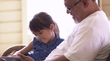 malajské : Girl using digital tablet with grandfather