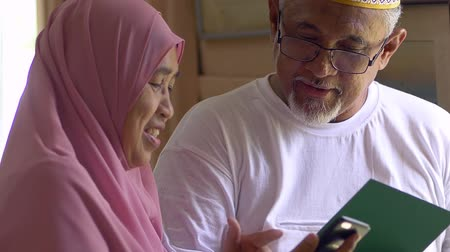 zaoblený : Senior couple with an Eid greeting card looking at smartphone