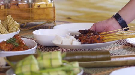 okurka : Hand placing down a plate of Satay