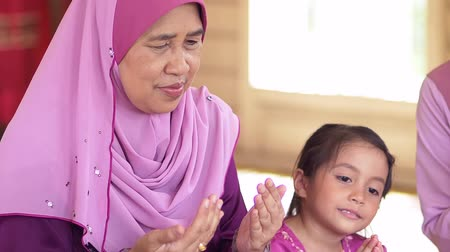 véu : Muslim senior woman and girl in praying posture