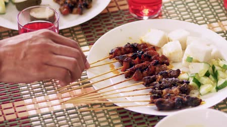 espetos : A plate of satay with ketupat and cucumber