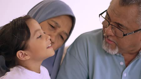 Young Muslim girl and her grandparents spending time together