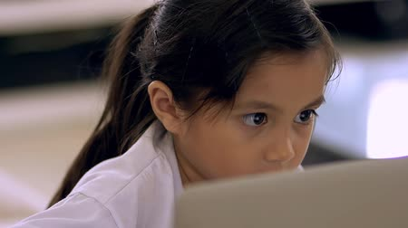 Close up of young girl using a laptop
