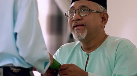 malaya : Young Muslim boy receiving green envelope from his grandfather