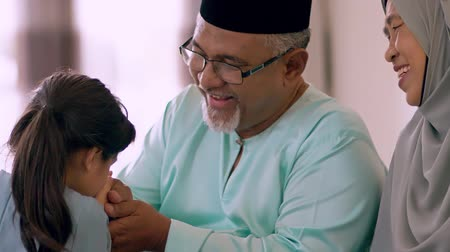 to celebrate : Young Muslim girl kissing hand of her grandfather