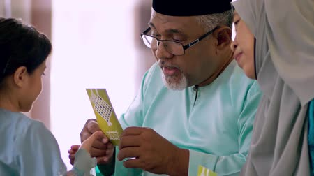 malaya : Young Muslim girl receiving green envelope from her grandparents Stok Video