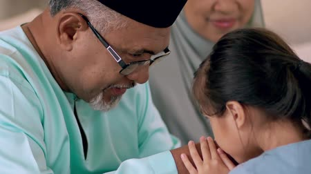 Young Muslim girl kissing hand of her grandfather