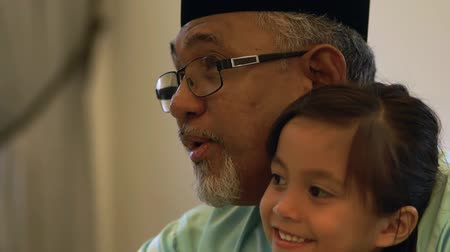 Senior Muslim man and his granddaughter spending time together