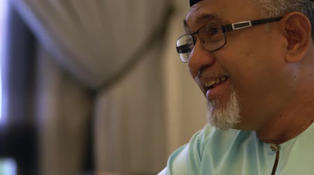 switching : Senior Muslim man holding a remote control