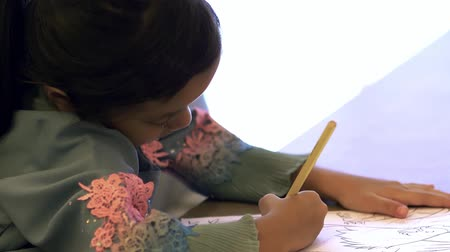 Muslim girl with coloring book Stock Footage