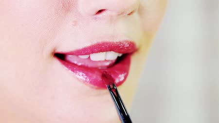 ruj : Woman putting on red colored lipstick