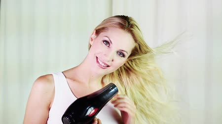 сушка : Cheerful woman blow drying her hair Стоковые видеозаписи