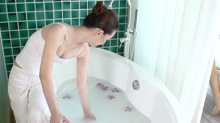 banyo : Woman checking the milk bath in bath tub Stok Video