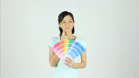 решение : Woman choosing suitable paint from colour chart