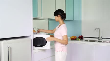 yansıma : Young woman heating up pastries in the microwave