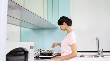домохозяйка : Woman cooking while man comes in to watch her prepare a meal Стоковые видеозаписи
