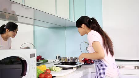 домохозяйка : Young woman preparing meal in the kitchen