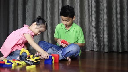 Boy and girl playing with colourful blocks