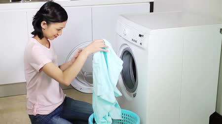 çamaşırhane : Woman putting laundry into a washing machine and starting the wash cycle