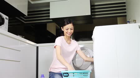 malajsky : Woman putting laundry into a washing machine and starting the wash cycle