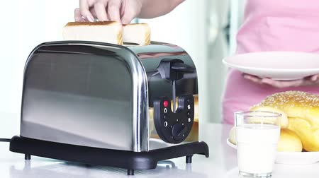 evcil : Woman putting bread in toaster