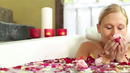 smell : Caucasian lady sniffing flowers while soaking in bath tub Stock Footage