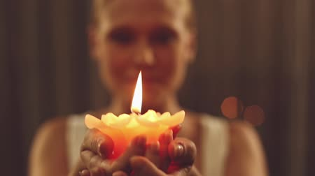 yanmak : Camera focus on lit candle held up by a caucasian woman