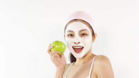 expressão facial : Woman with facial mask holding an apple
