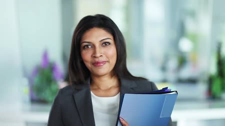 asian and indian ethnicities : A cheerful businesswoman looking at camera