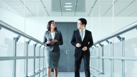 asian and indian ethnicities : Businessman and businesswoman walking together Stock Footage