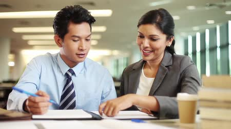 asian and indian ethnicities : Businessman and businesswoman having discussion Stock Footage