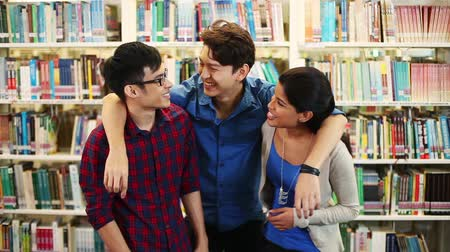 juventude : Three cheerful friends at a library