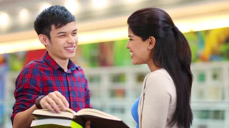 asian and indian ethnicities : Two friends discussing at library Stock Footage