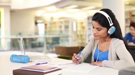 asian and indian ethnicities : Young student studying while listening to music Stock Footage