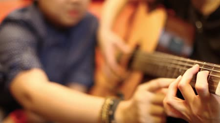 öğretim : Tutor is teaching a student how to play a guitar Stok Video