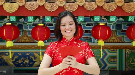 malajské : A cheerful Chinese woman giving a red packet