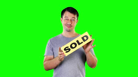 satılır : Mid adult man holding board saying SOLD Stok Video