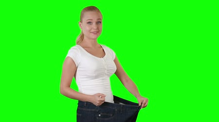 потеря : Slim and healthy young adult woman holding her big pants