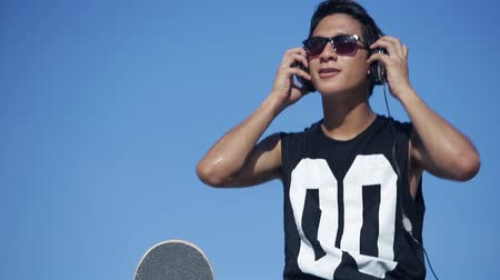 sluch : Young skateboarder listening to music