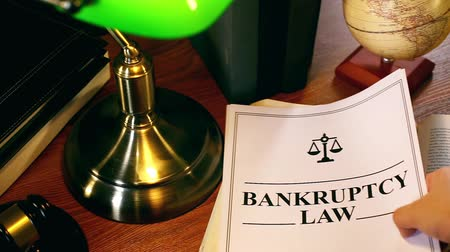 holding onto : Lawyer Putting Bankruptcy Law Document Onto Table