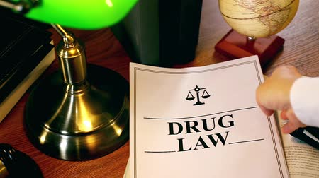 holding onto : Lawyer Putting Drug Law Document Onto Table