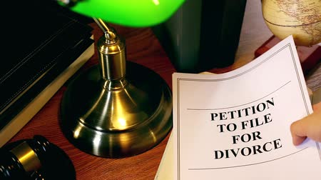 holding onto : Lawyer Putting Petition To File For Divorce Document Onto Table